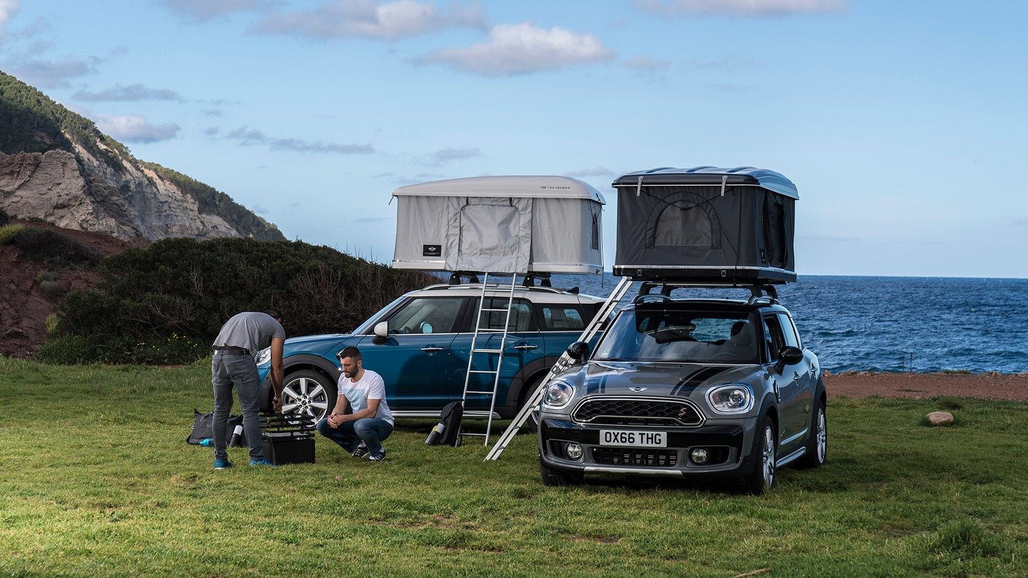 Two men with two Minis with rooftop tents next to the ocean.