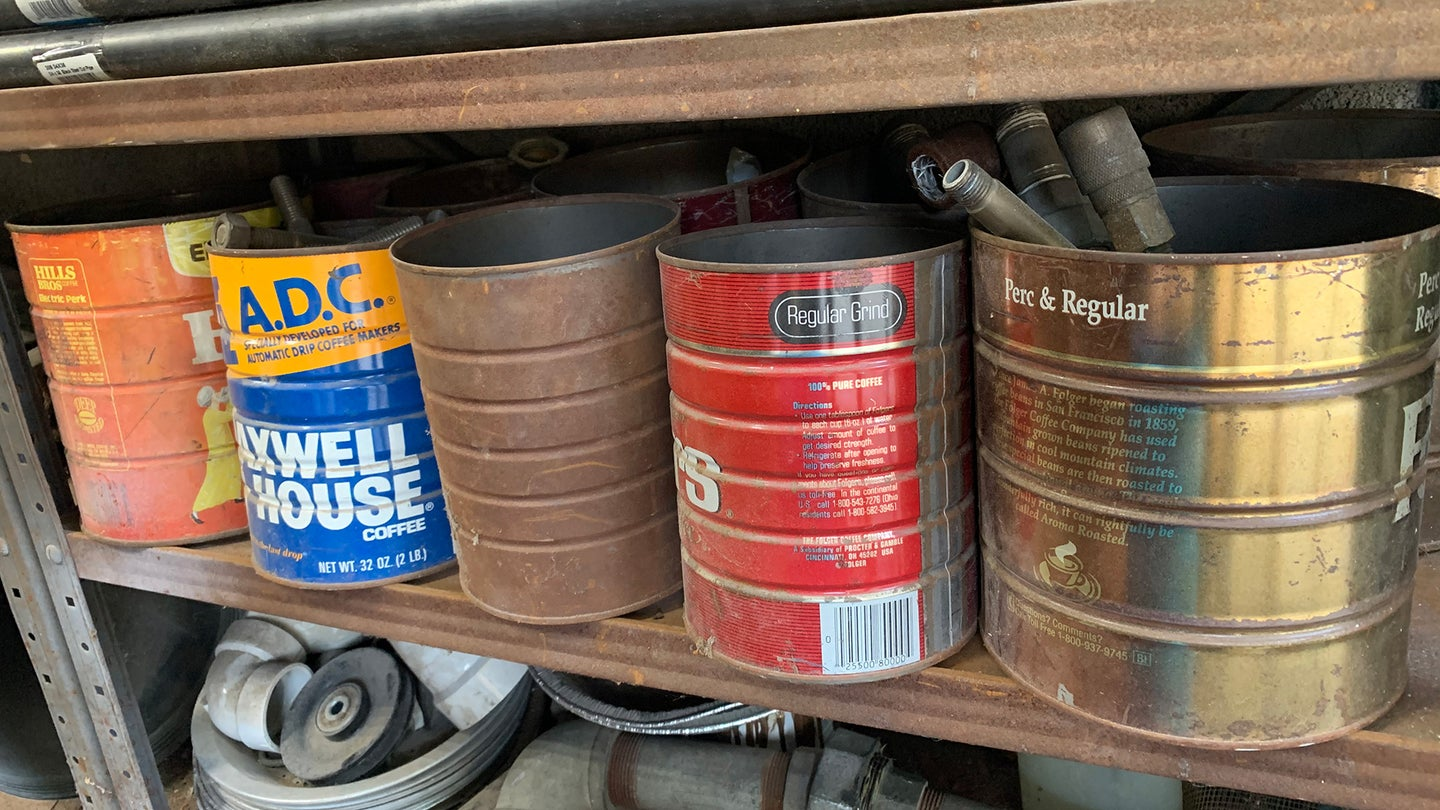 Four old metal coffee cans on a metal storage shelf in a garage.