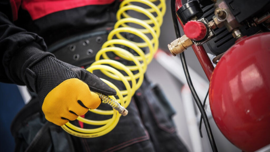 A mechanic holds a coiled yellow hose from an air compressor.