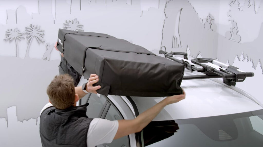 Two people put a rooftop tent on top of a vehicle's roof rack.