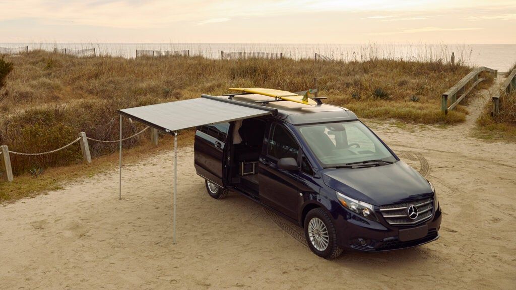 A Mercedes-Benz camper van with a yellow surfboard on top and a canopy.
