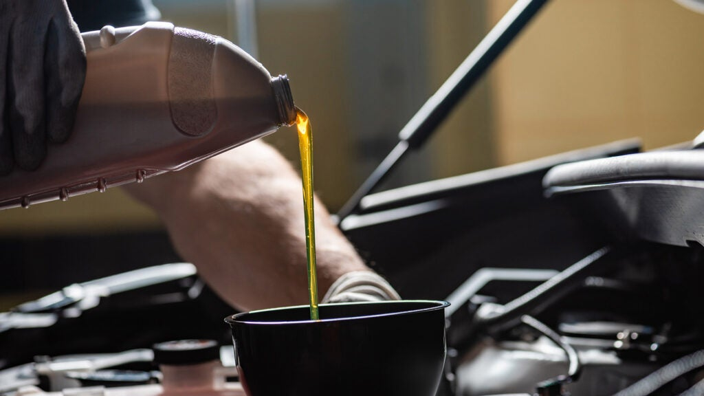 A mechanic pours new oil into the engine through a funnel.