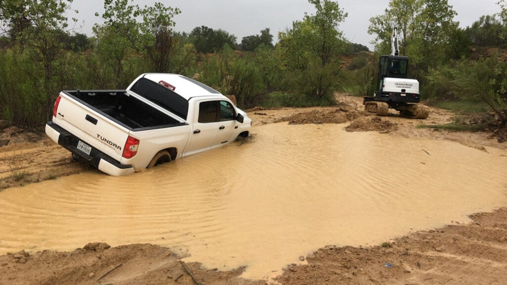 A white Toyota Tundra stuck in a giant mess of mud and a pool of water.