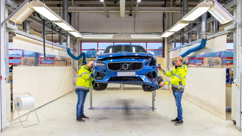 Two Volvo crash researchers inspect a blue wrecked car on a lift.