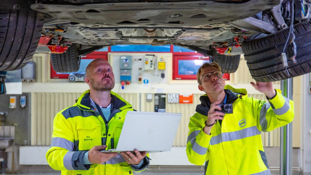 Two Volvo employees inspect the underside of a wrecked vehicle on a lift.