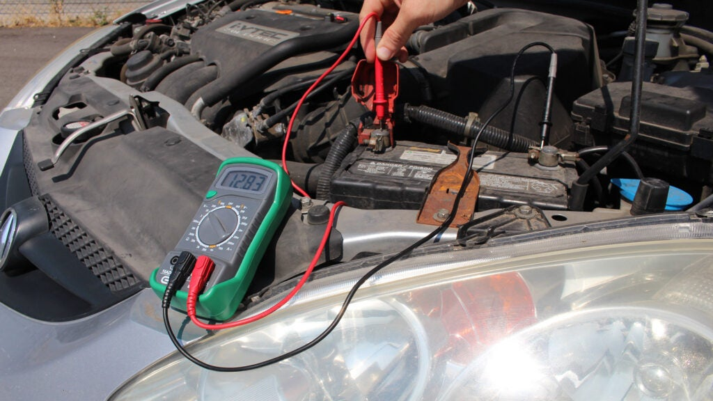 A multimeter is used to check battery voltage on a silver 2003 Acura RSX.