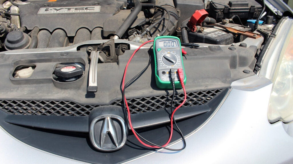A multimeter on the front part of an Acura RSX engine bay.