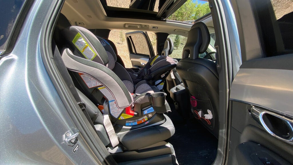 Three car seats in the back of a Volvo XC90 from the point of view of the rear passenger's side door.