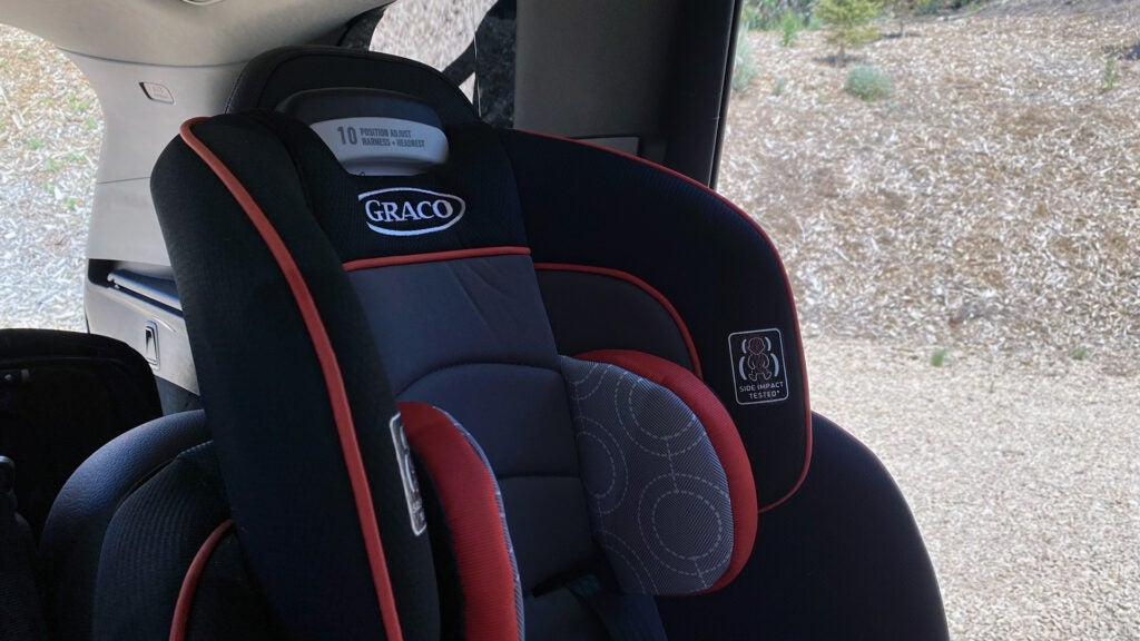 The head rest and bolsters of a child's car seat in the back of a Volvo XC90.