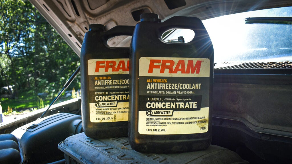 Two containers of Fram antifreeze on top of a '60s Dodge Charger engine block.