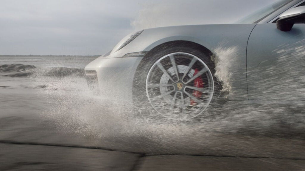 The front-end of a Porsche 911 driving through water.