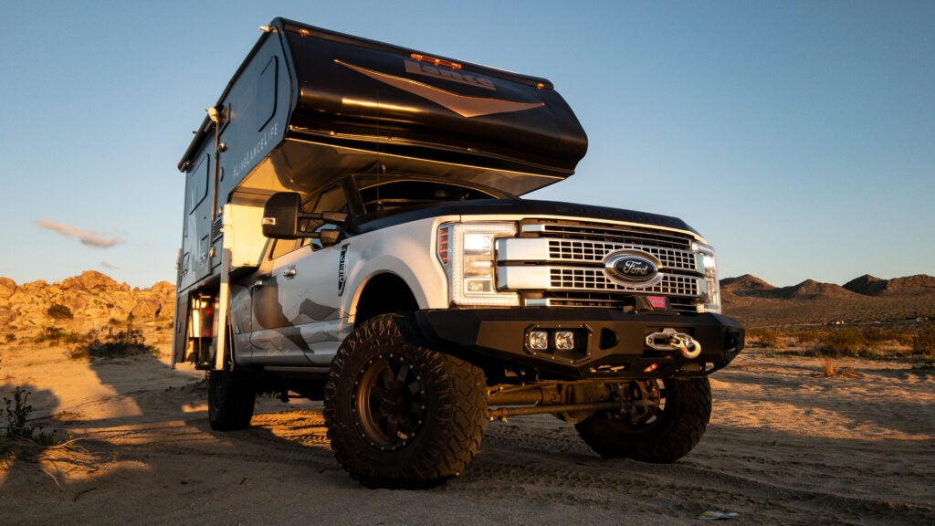 A truck camper on top of a massive Ford Super Duty.