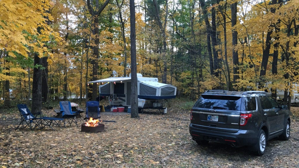 A Ford Explorer at a campsite with a popup camper a fire and camping chairs.