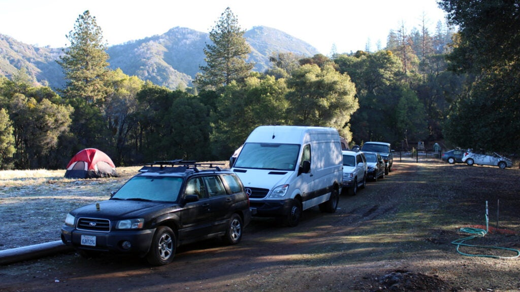 A caravan of cars and campervans at a campsite in California.