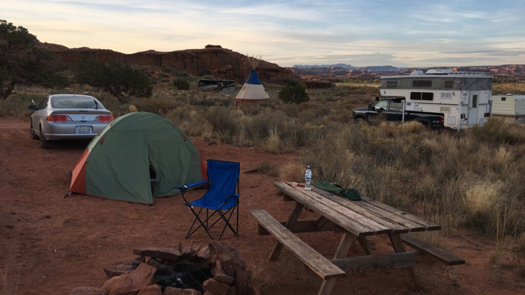 An Acura RSX, a tent, a picnic table, and a fire pit in the foreground of a campsite.