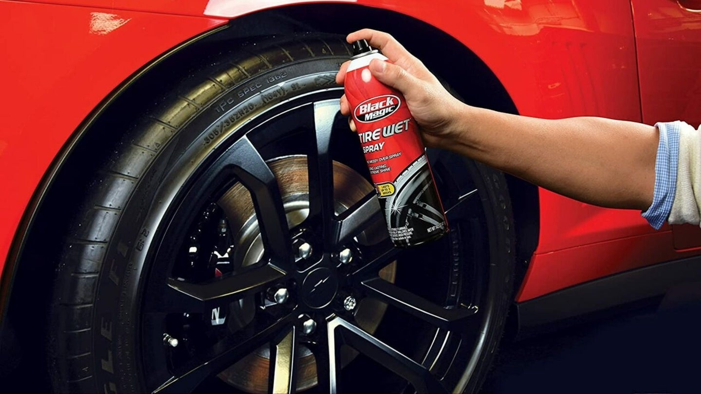 Cleaning tires of red car using tire shine product