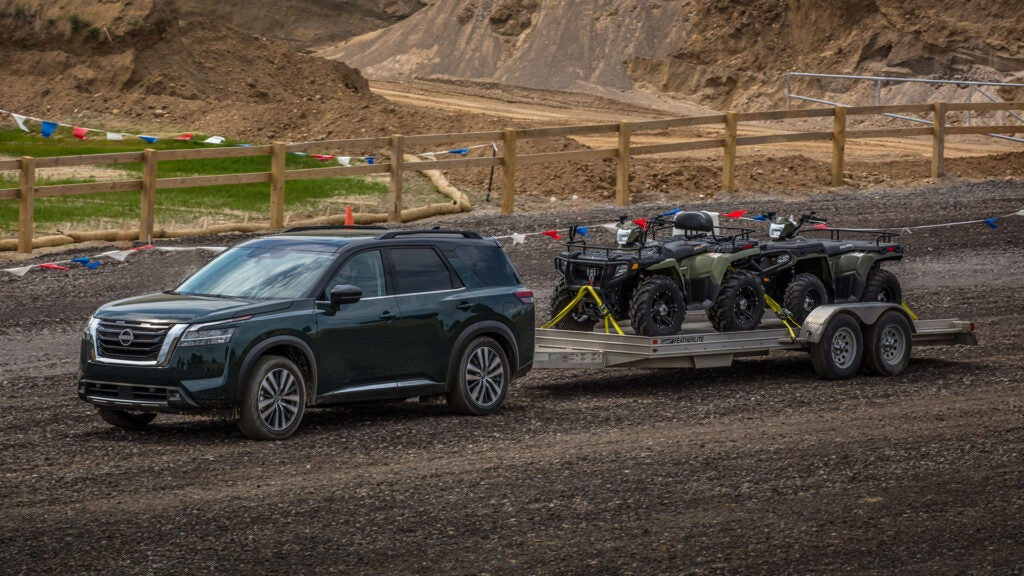 A Nissan Pathfinder tows two four wheelers.