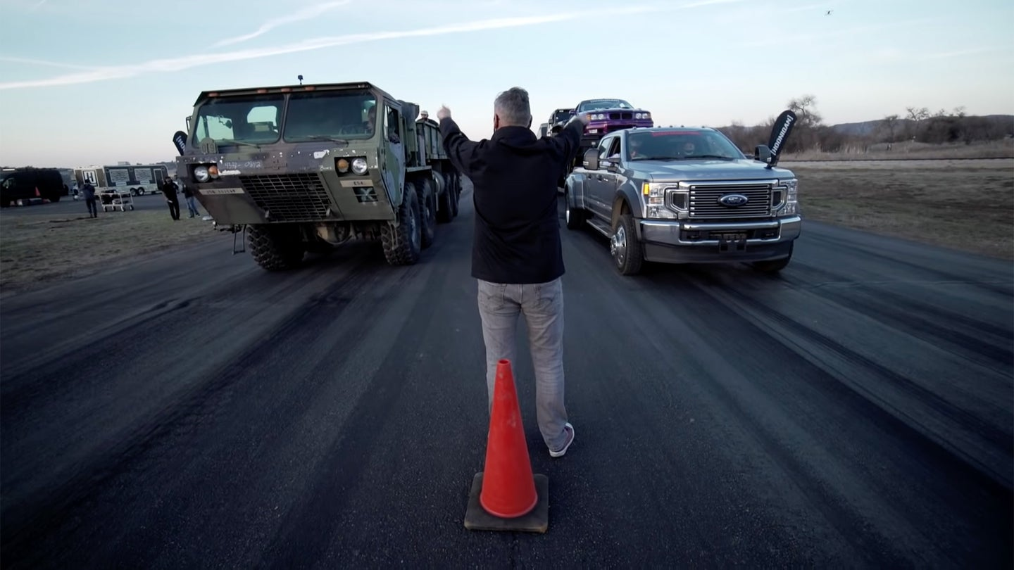 An 8x8 HEMTT lines up for a drag race against a Ford F-350 car hauler.