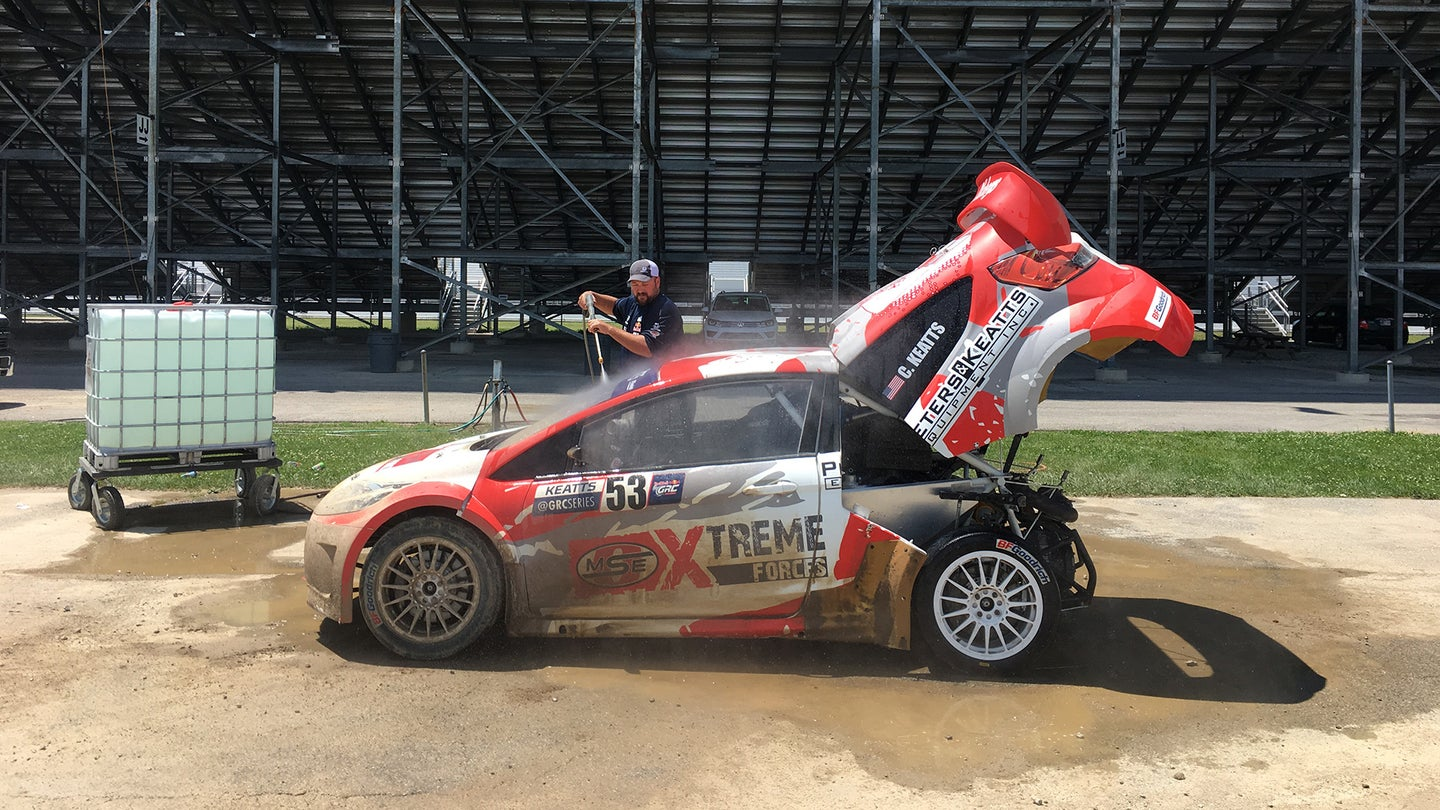 A person sprays down a global rallycross car with a portable water tank and a pressure washer.