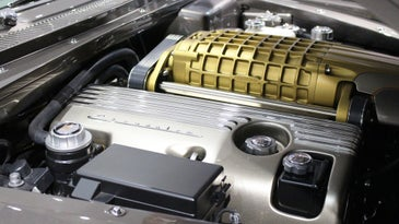 A gold supercharger in a custom engine bay by Chip Foose.