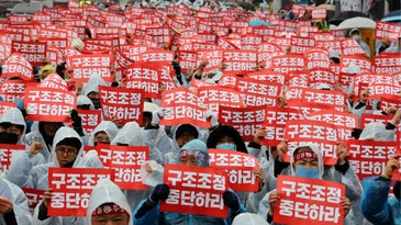 Union workers of GM Korea hold cards during a rally against the U.S. carmaker's plan to close the plant near the U.S. Embassy in Seoul, South Korea, Wednesday, Feb. 28, 2018. General Motors said on Feb. 13 it will close an underutilized factory in Gunsan, South Korea, by the end of May as part of a restructuring of its operations. The signs read: