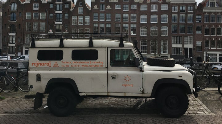 Land Rover Defender 110 delivery truck in the heart of Amsterdam next to the water.